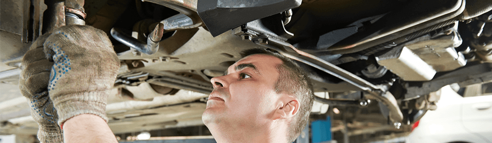 Mechanic servicing renault car exhaust